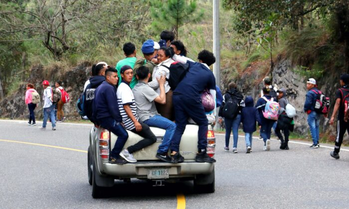 People, part of a caravan of migrants heading toward the United States, travel on the back of a truck as others walk along a road in Agua Caliente, Honduras, on Jan. 16, 2020. (Stringer/Reuters)