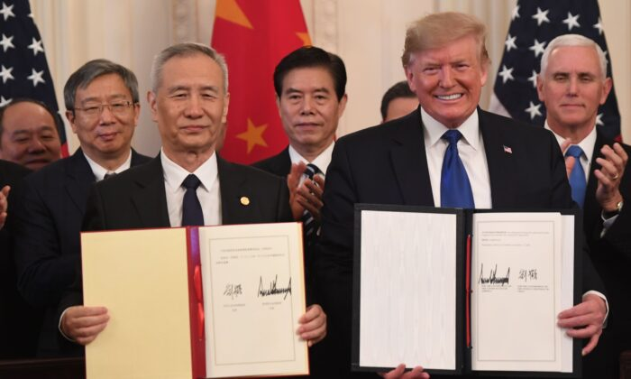 Chinese Vice Premier Liu He and U.S. President Donald Trump display the signed trade agreement between the United States and China in the East Room of the White House in Washington, on Jan. 15, 2020. (Saul Loeb/AFP/Getty Images)