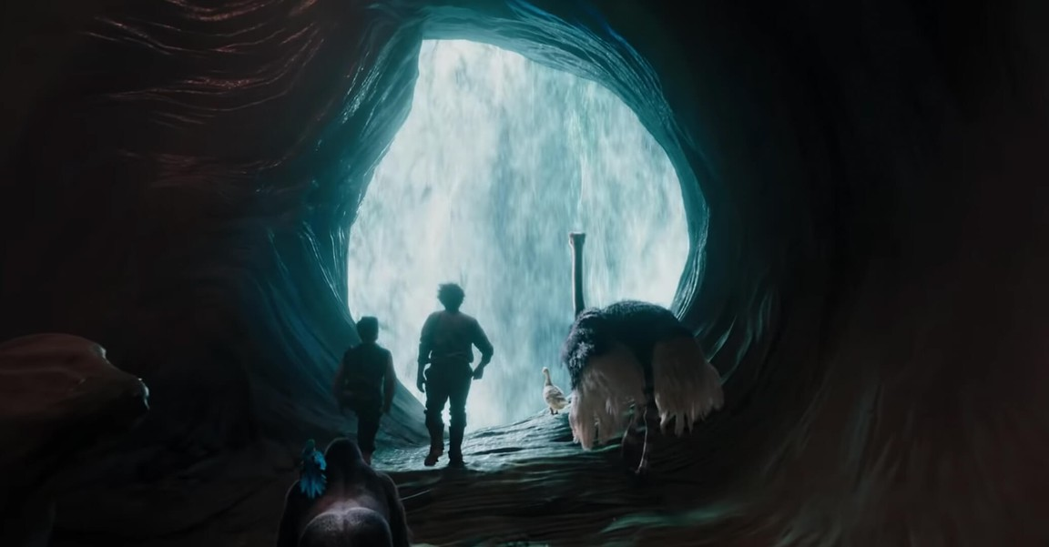 man, boy, and many animals in cave with waterfall