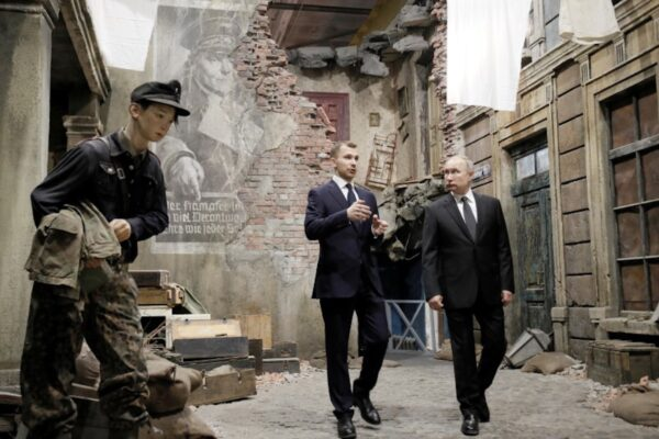 Russian President Vladimir Putin, right, examines an exhibition depicting a Berlin street after surrender in 1945 at 3D panorama 'Memory speaks.