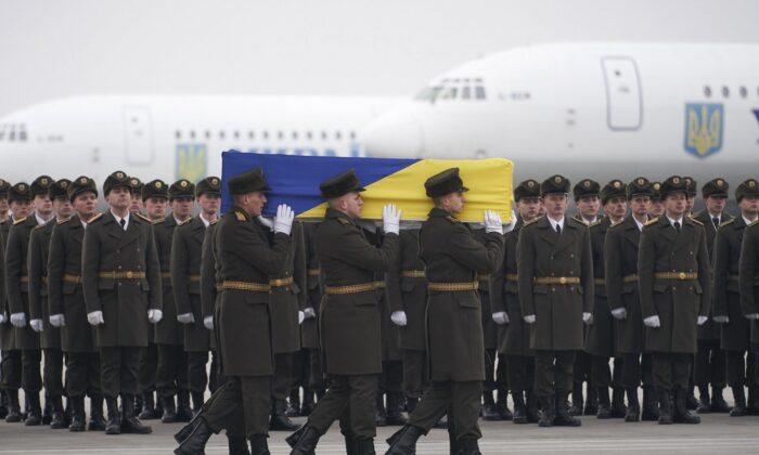 Honor guards carry a coffin of one of the eleven Ukrainian victims of the Ukrainian 737-800 plane during a memorial ceremony at Borispil International Airport outside Kyiv, Ukraine, on Jan. 19, 2020. (Ukrainian Presidential Press Office via AP)