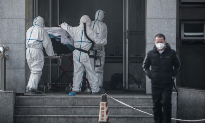 Medical staff members carry a patient into the Jinyintan hospital, where patients infected by a mysterious SARS-like virus are being treated, in Wuhan in China's central Hubei province on Jan. 18, 2020. (STR/AFP via Getty Images)