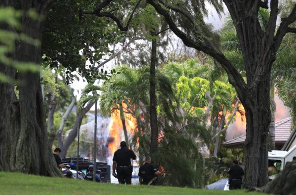 Honolulu police watch a house fire