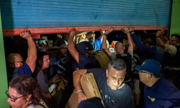Police arrive as people break into a warehouse filled with supplies in Ponce, Puerto Rico, on Jan. 18, 2020. (Ricardo Arduengo/AFP/Getty Images)