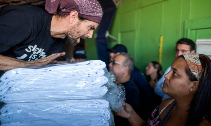 A man distributes supplies after breaking into a warehouse with supplies believed to have been from when Hurricane Maria struck the island in 2017 in Ponce, Puerto Rico, on Jan. 18, 2020. (Ricardo Arduengo/AFP via Getty Images)