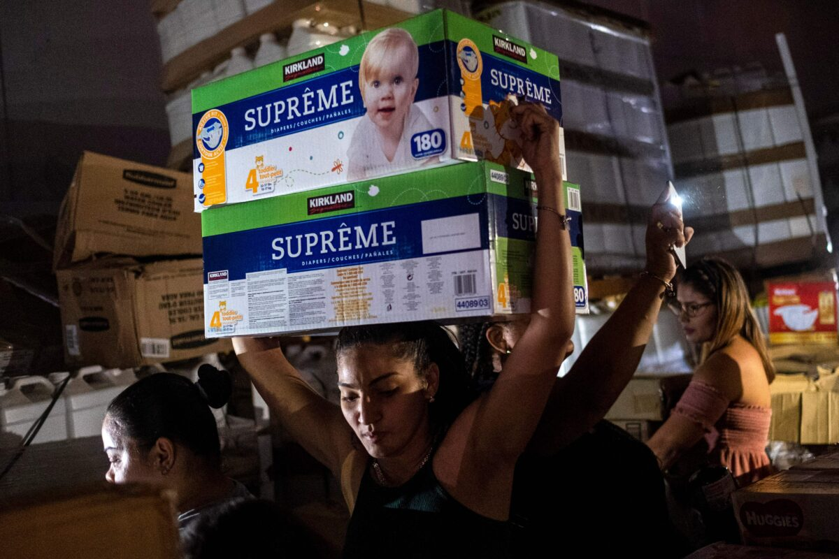 A woman carries boxes of baby diapers