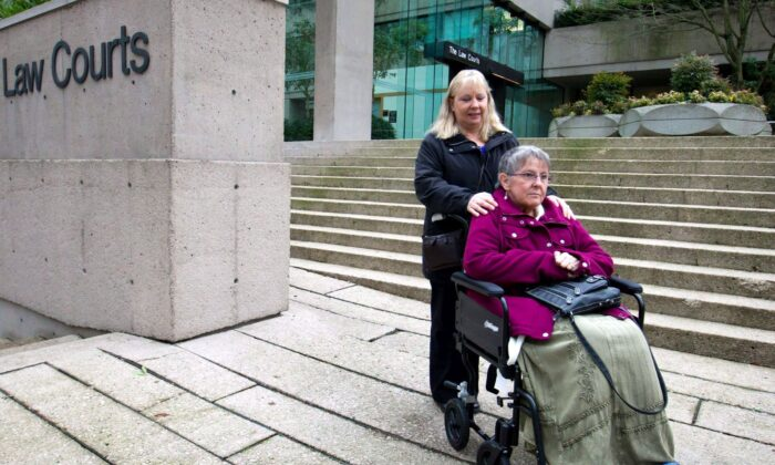 Gloria Taylor, assisted by her sister Patty Ferguson, pauses to talk to media outside the B.C. Supreme Court in Vancouver on Dec. 1, 2011. Taylor, who had Lou Gehrig's disease, was part of a legal battle to change the laws that criminalize doctor-assisted suicide. (The Canadian Press/Darryl Dyck)