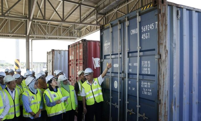 Malaysia's Environment Minister Yeo Bee Yin, third from left, inspects a container with plastic waste at a port in Butterworth, Malaysia, on Jan. 20, 2020. (AP Photo/Vincent Thian)