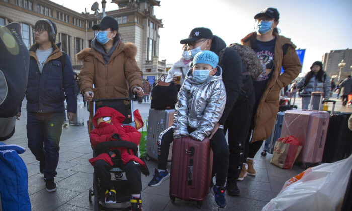 Travelers wear face masks as they walk outside of the Beijing Railway Station in Beijing on Jan. 20, 2020. (Mark Schiefelbein/AP)