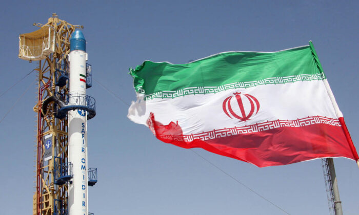 A picture taken on August 16, 2008 shows an Iranian flag fluttering in front of Iran's Safir Omid rocket, which is capable of carrying a satellite into orbit.(Vahidreza Alai/AFP via Getty Images)