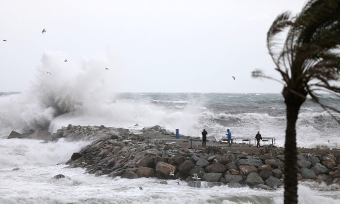 """People look at waves during the storm """"Gloria"""" on Barceloneta beach, in Barcelona, Spain, on Jan. 20, 2020. (Reuters/Nacho Doce)"""