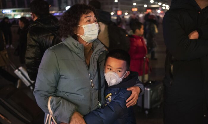 A Chinese boy hugs a relative as she leaves to board a train at Beijing Railway station in Beijing, China on Jan. 21, 2020. (Kevin Frayer/Getty Images)