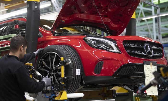 An employee mounts a wheel on a Mercedes Benz A Class on the assembly line at the Daimler AG factory in Rastatt, Germany, on Feb. 4, 2019. (Thomas Kienzle/AFP via Getty Images)