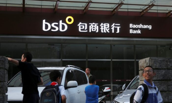People walk past a branch of Baoshang Bank in Beijing, China on Sept. 24, 2019. (Reuters)