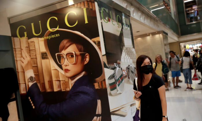 A woman walks past a Gucci advertising poster as shoppers and anti-government protesters gather at New Town Plaza in Sha Tin, Hong Kong, China on Nov. 3, 2019. (Shannon Stapleton/Reuters)