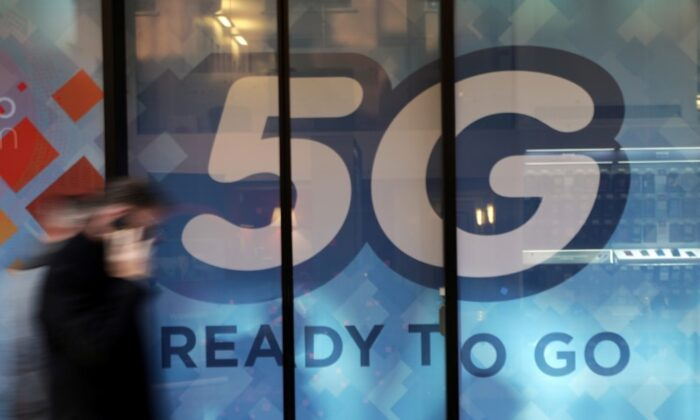 A man walks past a 5G sign in Monaco, on Nov. 28, 2019. (Eric Gaillard/Reuters)