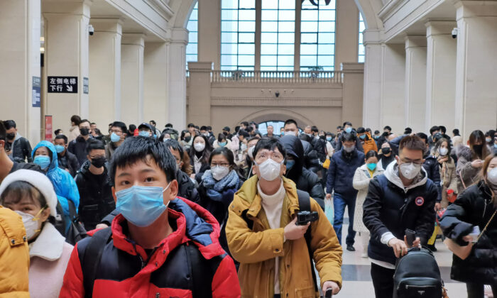"""People wear face masks as they wait at Hankou Railway Station in Wuhan City, China on Jan. 22, 2020. A new infectious coronavirus known as """"2019-nCoV"""" was discovered in Wuhan last week. (Xiaolu Chu/Getty Images)"""