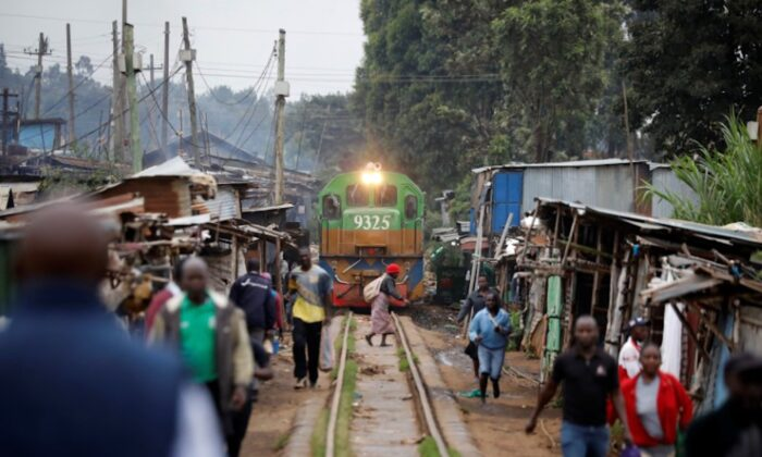 A woman crosses a railway track just as a train approaches a makeshift train station in the Kibera slum of Nairobi, Kenya, on Nov. 29, 2019. (Baz Ratner/Reuters)