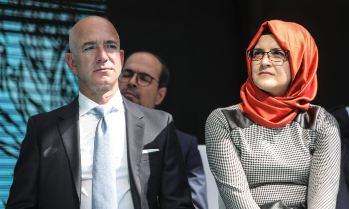 Amazon founder and Washington Post owner Jeff Bezos, left, sits with Hatice Cengiz, the fiance of Jamal Khashoggi, the Washington Post columnist who was killed, on the one year anniversary of Khashoggi's killing, in Stanbul, Turkey on Oct. 2, 2019. (Osman Orsal/Getty Images)