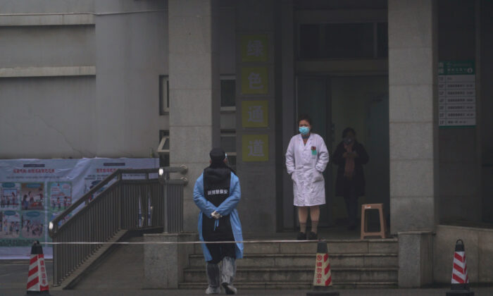 Hospital staff stand outside the emergency entrance of Wuhan Medical Treatment Center, where some infected with a new virus are being treated, in Wuhan, China, on Jan. 22, 2020. (Dake Kang/AP Photo)
