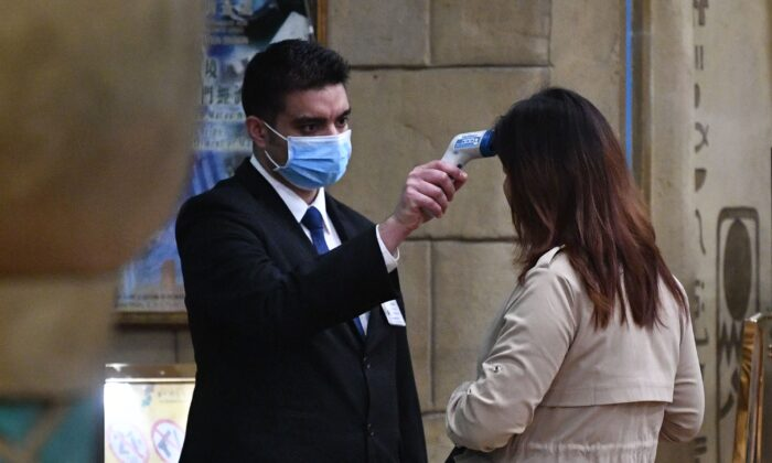 A staff member checks the temperature of a guest entering the casino of the New Orient Landmark hotel in Macau after the former Portuguese colony reported its first case of the new SARS-like virus that originated from Wuhan in China, on Jan. 22, 2020. (Anthony Wallace/AFP via Getty Images)