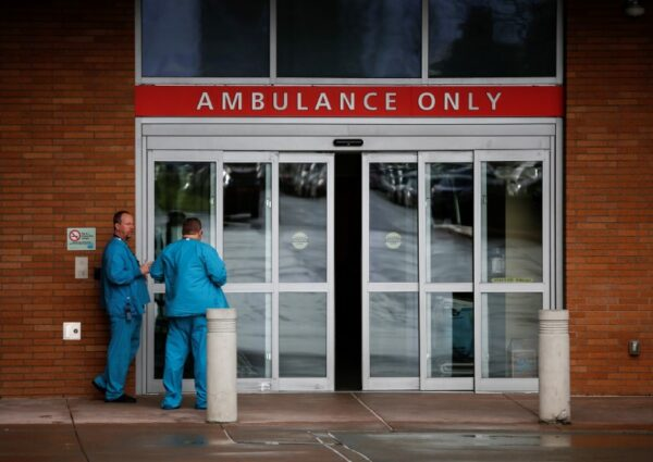 Employees in scrubs talk next to the ambulance entrance at Providence Regional Medical Center after coronavirus victim treated in Everett