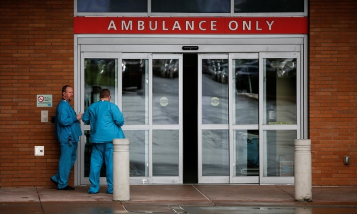 Employees in scrubs talk next to the ambulance entrance at Providence Regional Medical Center in Everett, Wash., on Jan. 21, 2020. (Lindsey Wasson/Reuters)