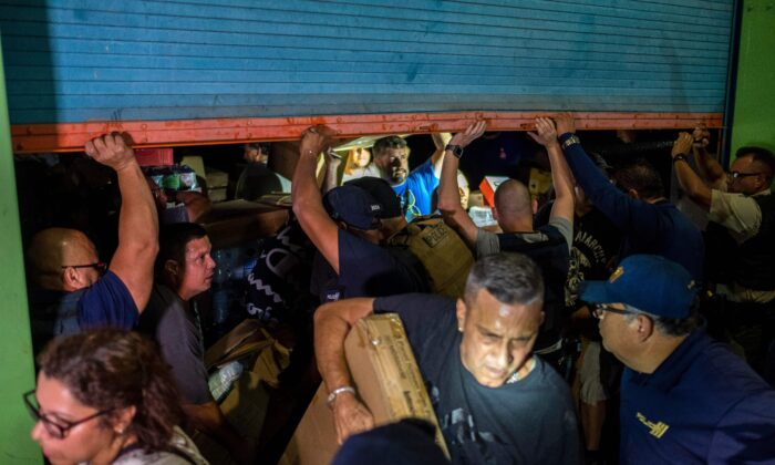 Police arrive as people break into a warehouse filled with supplies, believed to have been from when Hurricane Maria struck the island in 2017 in Ponce, Puerto Rico, on Jan. 18, 2020. (Ricardo Arduengo/AFP via Getty Images)