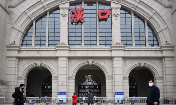 People walk past the closed Hankou Railway Station after the city was locked down following the outbreak of a new coronavirus in Wuhan, Hubei province, China, on Jan. 23, 2020. (China Daily via Reuters)