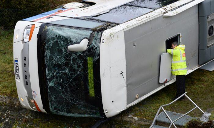 A police officer investigates a school bus that has crashed in Berka Vor Dem Hainich, near Eisenach, Germany, on Jan. 23, 2020. (Swen Pfoertner/dpa via AP)