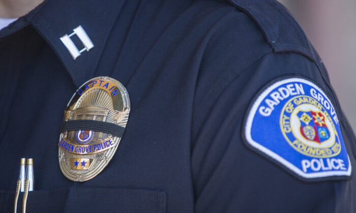 A police officer wears a badge with a mourning band during a press conference in front of the Garden Grove Police Department in Garden Grove, Calif. on Aug. 8, 2019. (Apu Gomes/AFP via Getty Images)