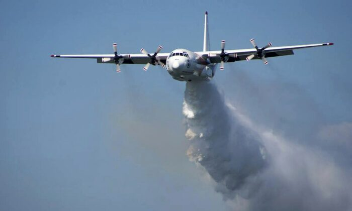 "In this undated photo released from the Rural Fire Service, a C-130 Hercules plane called ""Thor"" drops water during a flight in Australia. Officials in Australia on Jan. 23, 2020, searched for a water tanker plane feared to have crashed while fighting wildfires. (RFS via AP)"