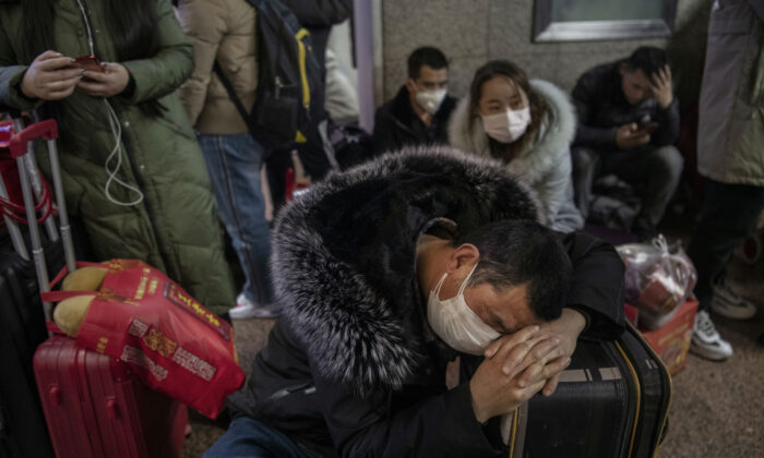 A Chinese man wears a protective mask as he sleeps before boarding a train before the annual Spring Festival at a Beijing railway station in Beijing, China, on Jan. 23, 2020. (Kevin Frayer/Getty Images)