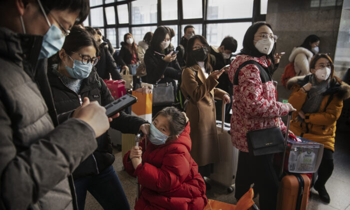 Chinese travelers wear protective masks as they wait before boarding a train before the annual Spring Festival at a Beijing railway station on Jan. 23, 2020. (Kevin Frayer/Getty Images)