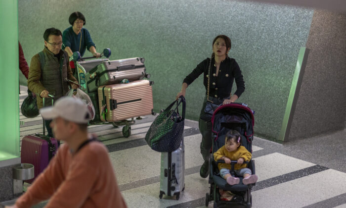 People arrive to Los Angeles International Airport after touchdown of an Air China flight from Beijing, which serves as a connector from Wuhan, China to Los Angeles, on the first day of health screenings for coronavirus of travelers from Wuhan, on Jan. 18, 2020. (David McNew/Getty Images)
