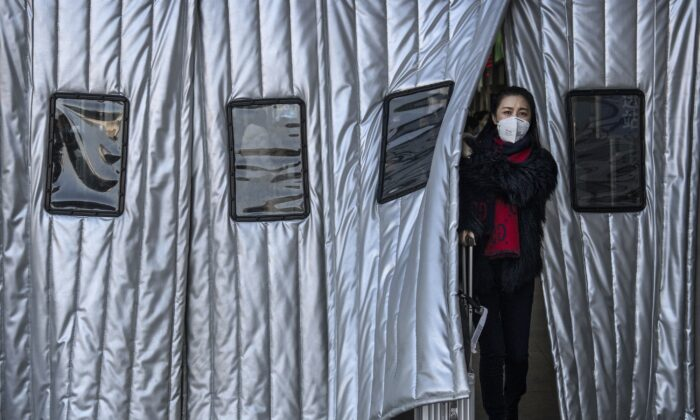 A Chinese woman wears a protective mask as she leaves a Beijing railway station in China on Jan. 23, 2020. (Kevin Frayer/Getty Images)