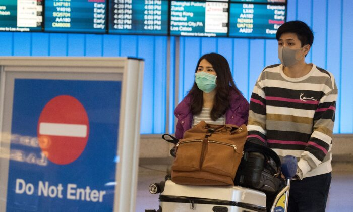 Passengers wear protective masks to protect against the spread of the coronavirus as they arrive at the Los Angeles International Airport, California, on Jan. 22, 2020. (Mark Ralston/AFP via Getty Images)