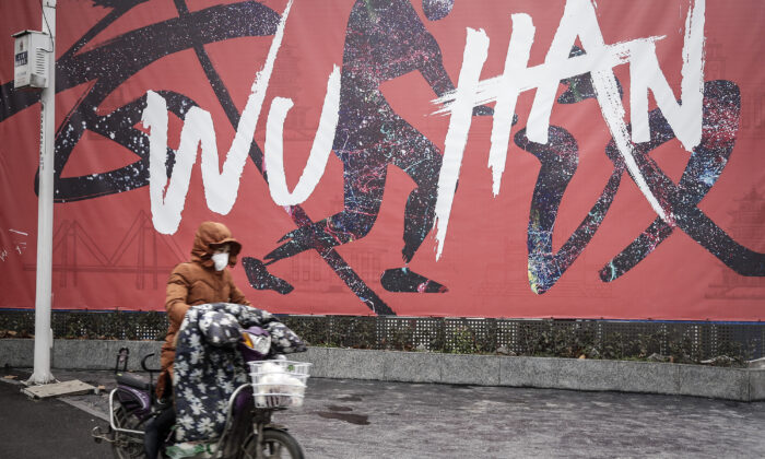 A woman wears a mask while riding an electric bicycle in Wuhan, Hubei Province, China, on Jan. 22, 2020. (Getty Images)