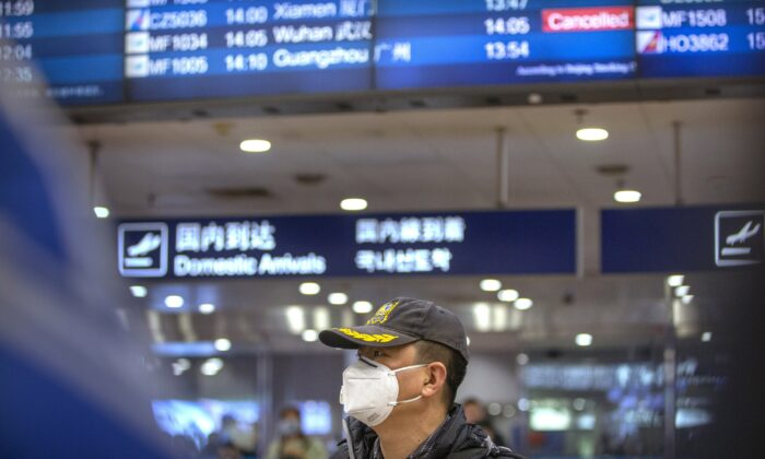 A traveler wears a face mask beneath an information display showing a canceled flight from Wuhan at Beijing Capital International Airport in Beijing on Jan. 23, 2020. (Mark Schiefelbein/AP Photo)