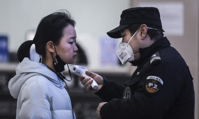 Security personnel check the temperature of passengers in the Wharf at the Yangtze River in Wuhan, Hubei Province, China, on Jan. 22, 2020. (Getty Images)