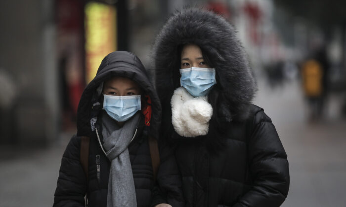 A family wears masks while walking in the street in Wuhan, Hubei province, China, on Jan. 22, 2020. (Getty Images)