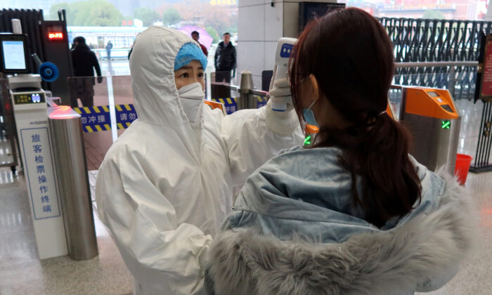 A worker in protective suits checks the temperature of a passenger arriving at the Xianning North Station on the eve of the Chinese Lunar New Year celebrations, in Xianning, a city bordering Wuhan to the north, in Hubei province, China, on Jan. 24, 2020. (Reuters/Martin Pollard)