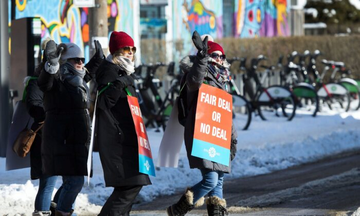 Teachers of the Elementary Teachers' Federation of Ontario wave to passing cars as they participate in a full withdrawal-of-services strike in Toronto on Jan. 20, 2020. (The Canadian Press/Nathan Denette)