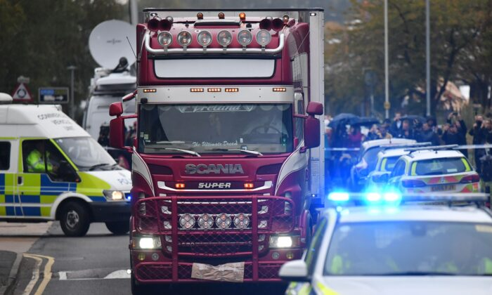 Police officers drive away a lorry (C) in which 39 dead bodies were discovered sparking a murder investigation at Waterglade Industrial Park in Grays, east of London, Britain, on Oct. 23, 2019. (Ben Stansall/AFP via Getty Images)