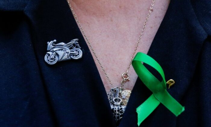 A motorcycle pin is seen on the shirt of Charlotte Charles, the mother of British teen Harry Dunn who was killed in a car crash on his motorcycle, during an interview in the Manhattan borough of New York City, on Oct. 15, 2019. (Eduardo Munoz/Reuters)