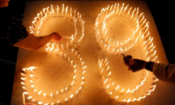 Catholic believers light candles during a mass payer for 39 Vietnamese people found dead in a truck near London, at a church in Nghe An province, Vietnam, on Nov. 30, 2019. (Kham/ Reuters)