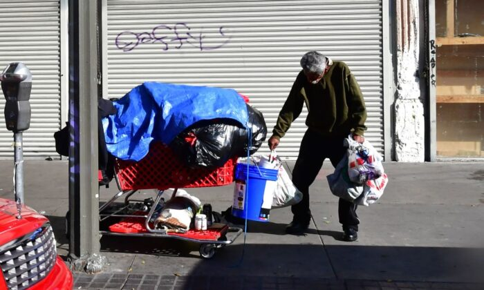 A homeless man stands with a cart of his belongings on a street in Los Angeles, Calif., on Jan. 8, 2020. (Frederic J. Brown/AFP via Getty Images)