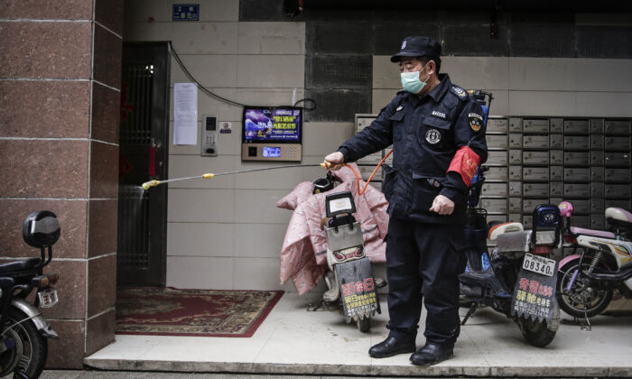 A security is using alcohol to disinfect in a community in Wuhan City, China on Jan. 23, 2020. (Getty Images)