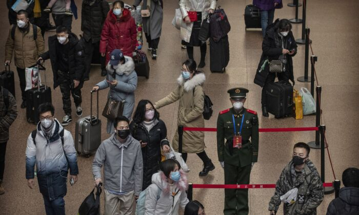 A Chinese police officer wears a protective mask as passengers, many wearing masks also, arrive to board trains at a Beijing railway station in Beijing, China on Jan. 23, 2020. (Kevin Frayer/Getty Images)