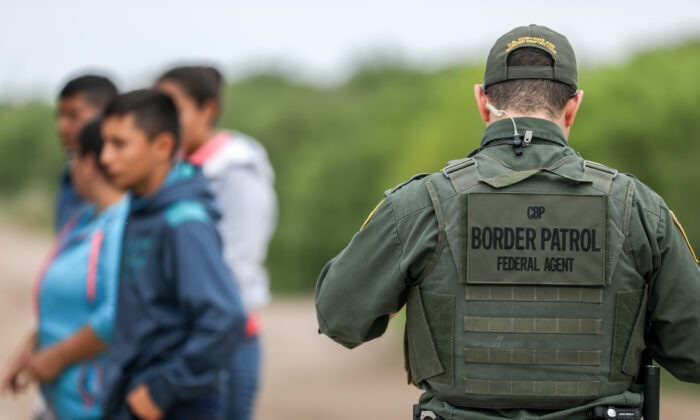 A Border Patrol agent apprehends illegal aliens who have just crossed the Rio Grande from Mexico into Penitas, Texas, on March 21, 2019. (Charlotte Cuthbertson/The Epoch Times)